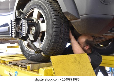 Cheriton, Kent/UK-August 14 2018: Tyre/tire fitting — a mechanic on the underside of a vehicle adjusting the tie-rod to align the wheel correctly