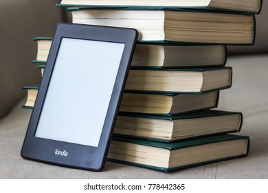 CHERKASSY, UKRAINE - APRIL 23, 2016: Amazon Kindle paperwhite reader over big stack of books.
