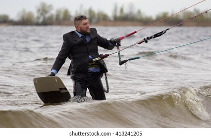 Cherkasy, Ukraine - APRIL 21, 2016: Male office workers in suits ride kites. Business and Sports Festival