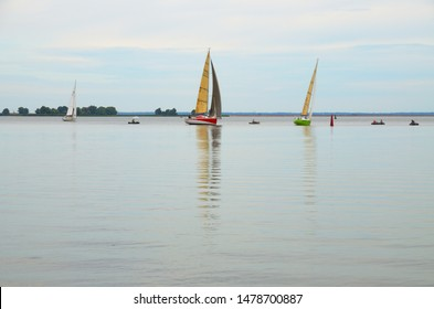 Cherkasy, Ukraine - August 11 2019: Sailing regatta. Three boats on the horizon against a light blue sky are approaching the pivot point. Calm water in the foreground.