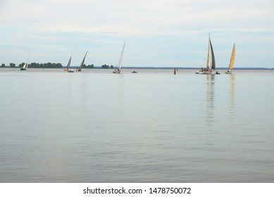 Cherkasy, Ukraine - August 11 2019: Sailing regatta. A group of yachts in calm water on the horizon against a light blue sky is approaching a pivot point.