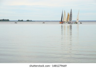 Cherkasy, Ukraine - August 11 2019: Sailing regatta. Yacht race near the turning point. Reflection on the water in the foreground.
