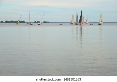 Cherkasy, Ukraine - August 11 2019: Sailing regatta. Competition of yachts. Three yachts are approaching and six are moving away from the return point.