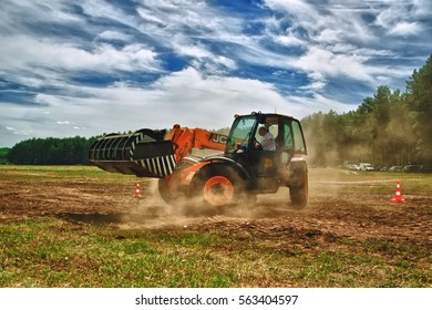 Cherkasy, Ukraine - June 12, 2012: Work on red tractor loader JCB . Tractor rides on the field on forest background.