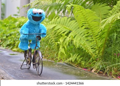 Cherkasy, Ukraine, June 13, 2019 - Toy Cookie monster funny riding a black bike on the path among the plants