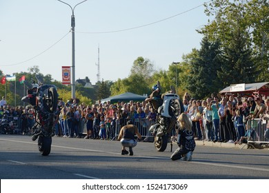 Cherkasy, Ukraine - September 14 2019: City Day celebration. Moto show. Stunt driver rides on the rear wheel of a motorcycle sitting on the steering wheel. Many viewers watch and shoot on camera.