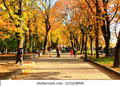 Chernihiv Ukraine. 16 October 2017: Central city park with people walking on alley with benches in autumn. Autumn with yellow foliage on trees. People walk on autumnal city park. People rest in park