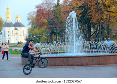 Chernihiv / Ukraine. 19 October 2018:  Modern guy riding bicycle in city park with fountains. Modern youth is resting in the park. Youth entertainment. young guy rides bicycle along city alley