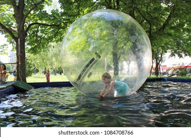Chernihiv / Ukraine. 24 May 2014: Little girl playing for a drive in transparent sphere. Kid playing on water. Happy childhood. 24 May 2014 in Chernihiv / Ukraine