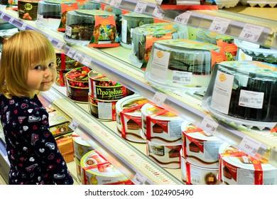 Chernihiv / Ukraine. 26 August 2017: Little girl choices a cake on the shelves of supermarket. 26 August 2017 in Chernihiv / Ukraine.
