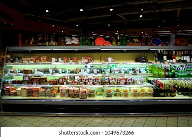 Chernihiv / Ukraine. 26 August 2017: Wide choice of different cakes and alcoholic drinks on shelves of transparent refrigerator of supermarket. 26 August 2017 in Chernihiv / Ukraine.