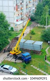 Chernihiv / Ukraine. 28 May 2015: Industrial crane lift up container box to load it onboard truck. Crane raising container to load it in truck in city yard. 28 May 2015 in Chernihiv / Ukraine.