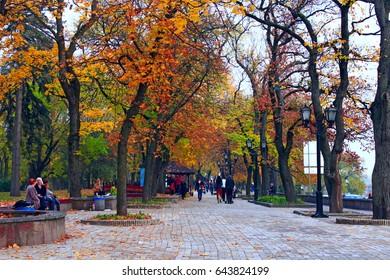 Chernihiv / Ukraine, Circa October 2016. People have a rest in the beautiful park of Chernihiv with promenade paths, lanterns and big trees. Chernihiv / Ukraine, Circa October 2016.