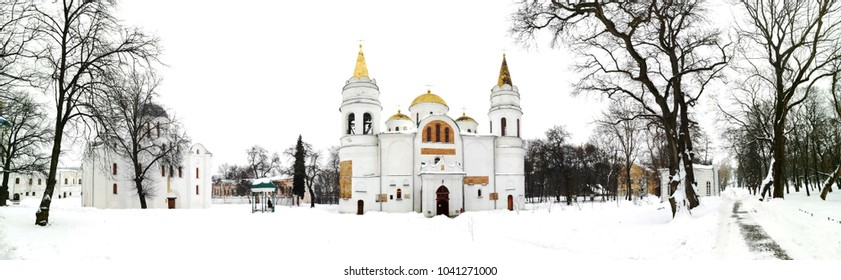 Chernihiv, Ukraine. The Savior Transfiguration Cathedral of Chernihiv and Borys and Hlib Cathedral behind the tree branches in winter with white snow. Cloudy day in Chernihiv, Ukraine