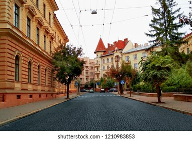 Chernivtsi center, Universytetska Street, old town architecture with green summer trees and pavement