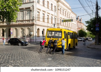 Chernivtsi, Chernivtsi / Ukraine - 04 28 2018: Four men, pushing a bus