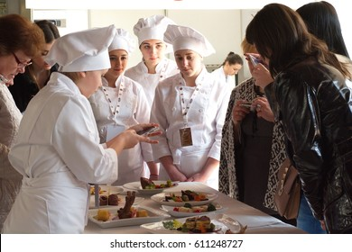 CHERNIVTSI, UKRAINE -29 MARCH: Female chefs in white jackets and guests make photo of prepared dishes on festival of culinary art Bukovina Food Land 2017. Chernivtsi, Ukraine, March 29, 2017