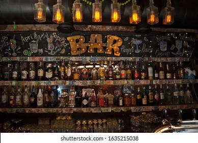 """Chernivtsi, Ukraine. December 27, 2019. Bar: """"Vyo"""". 16. Kobylianska Street 16. Alcohol bottles on shelves behind bar counter."""