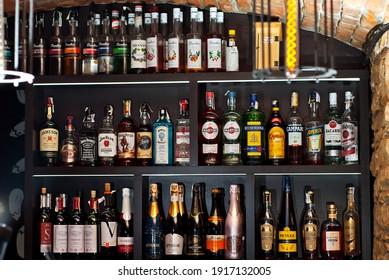 """Chernivtsi, Ukraine. February 8, 2021. Bar: """"BAKLAJAN"""". Olga Kobylianska Street 38. Alcohol bottles on shelves behind bar counter."""