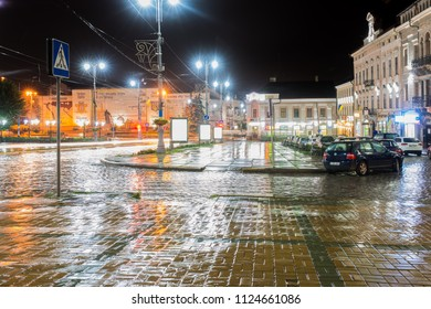 CHERNIVTSI, UKRAINE - JUN 30, 2018: The central square  in the night during the rain. Blur background of street road. Night lights on the Golovna streets of Chernivtsi.