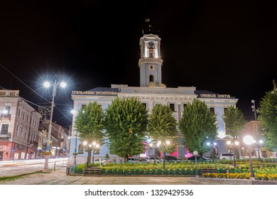 CHERNIVTSI, UKRAINE - JUN 30, 2018: City Hall. The central square in the night. Blur background of street road. Night lights on the Golovna streets of Chernivtsi.