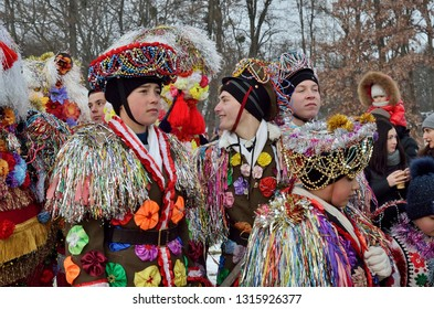 CHERNIVTSI,BUKOVINA,UKRAINE - JANUARY 13, 2019:Young men sing Christmas and Malanka songs during ethnic festival in open-air museum of folk architecture.Man dressed in carnival  costume decorated with