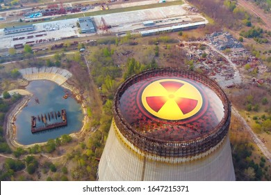 Chernobyl disaster. Radioactive zones near the reactor in Chernobyl. Sign of radiation on the background of the cooling tower in Chernobyl. Radiation contamination area near the Chernobyl reactor.