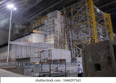 Chernobyl Exclusion Zone, Ukraine - JUL 02, 2019: EBRD Media visit to The New Safe Confinement above remains of reactor 4 and the old sarcophagus at Chernobyl nuclear power plant, 2 July 2019