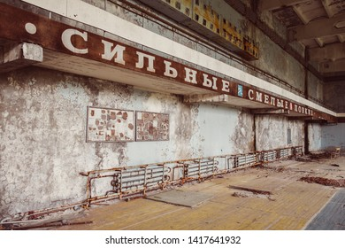 Chernobyl Exclusion Zone / Ukraine - July 2016: School gym in destroyed abandoned ghost city Pripyat ruins after disaster. Fallout lost town, apocalyptic building. Text translation: Strong Brave Deft.