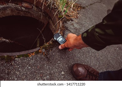 Chernobyl Exclusion Zone / Ukraine - July 2016: Man holding in hand a Geiger counter, measures radiation level in abandoned ghost city Pripyat ruins after Nuclear Power Plant atomic reactor disaster.