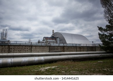 CHERNOBYL, UKRAINE - APRIL 15, 2019 : View of the destroyed Reactor 4 and the Memorial for the Chernobyl liquidators, Chernobyl exclusion zone