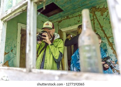 Chernobyl, Ukraine - July 2nd 2018 - Group of tourists taking pictures of the left overs in Chernobyl area, the city became famous after the nuclear incident in 1986.