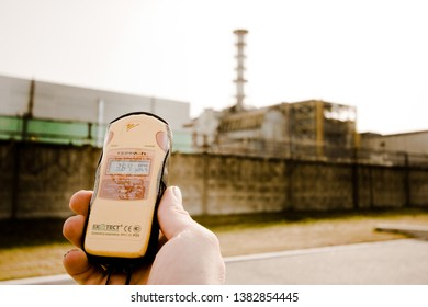 Chernobyl / Ukraine - October 2009 , A Geiger counter dosimeter in hand in front of nuclear power plant infamous for tragedy