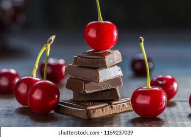 Cherries and broken chocolate on a dark background.