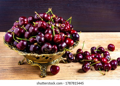 Cherries in a bronze vase on a wooden table against a black background