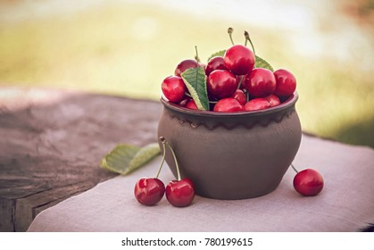 Cherries in ceramic bowl. Red cherry & leaf in bowl on wooden background with sunlight. Fresh cherries bowl as healthy fruitarians concept. Sweet organic berries on old rustic stump. Juicy tasty fruit