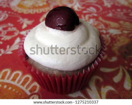 Cherries and cream cupcake with white frosting and cherry garnish