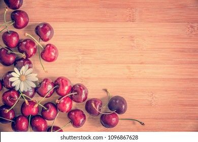 Cherries and daisy on wood background with copy space