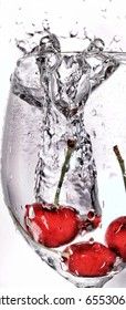 Cherries dropped in a wine glass of water