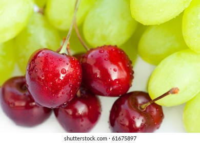 cherries with drops of water and grapes isolated on white