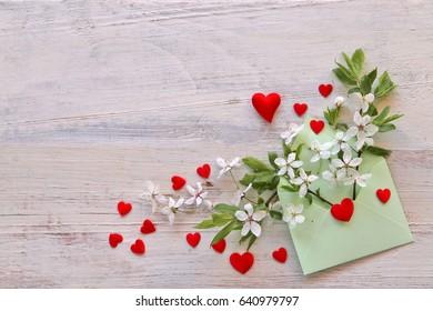 Cherries flowers , hearts in envelope on wooden background