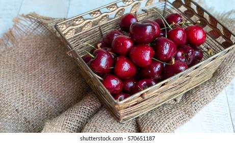 Cherries in gold basket on hemp , Fresh cherries with drop water in basket