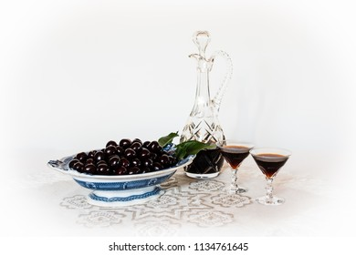 Cherries on an old china dish and a crystal carafe and glasses with cherry brandy on a table cloth with a white background, a still life.