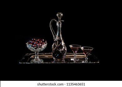 Cherries on an old crystal bowl and a crystal carafe and glasses with cherry brandy on a silver dish with a black background, a still life.