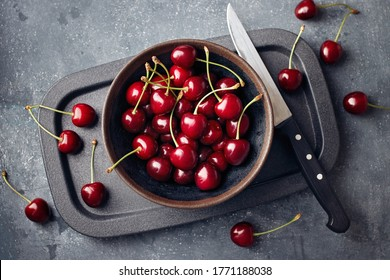 Cherries in a small bowl and scattered around the table.