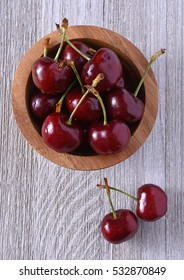 Cherries in a wooden bowl on a white table