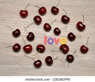 Cherries with the word love on a wooden background