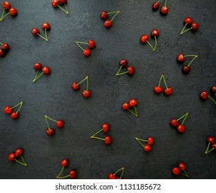 Cherry background. Pattern of fresh berries on a black table with drops of water. View from above. Flat lay, top view.