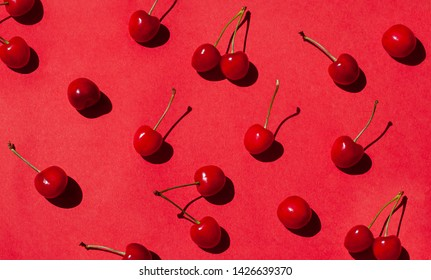 Cherry berries on the red background on the noon sun. Summer food pattern. Top view