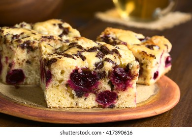 Cherry blondie or blond brownie cake baked with white and dark chocolate pieces, photographed with natural light (Selective Focus, Focus on the front of the first cake piece)